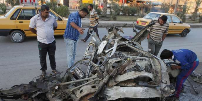 Des Irakiens constatent les dégâts provoqués par les attentats revendiqués par une branche d'Al-Qaida à Bagdad, le 28 octobre 2012.