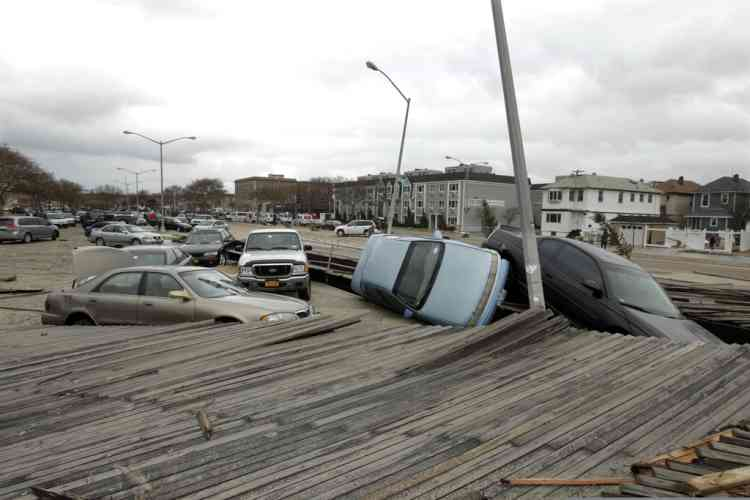 Pedestrians walk past the boardwalk and cars displaced by superstorm Sandy, near Rockaway Beach in the New York City borough of Queens Tuesday, Oct. 30, 2012, in New York. Sandy, the storm that made landfall Monday, caused multiple fatalities, halted mass transit and cut power to more than 6 million homes and businesses. (AP Photo/Frank Franklin II)