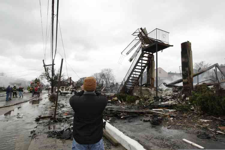 A man photographs damage caused by a fire fire in the Belle Harbor neighborhood in the New York City borough of Queens Tuesday, Oct. 30, 2012, in New York. Sandy, the storm that made landfall Monday, caused multiple fatalities, halted mass transit and cut power to more than 6 million homes and businesses. (AP Photo/Frank Franklin II)