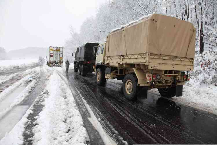 Snow plows and the Army National Guard arrive on Interstate 68 as heavy duty towing vehicle move stranded trucks and clear snow from the road, Tuesday, Oct. 30, 2012, in Preston County, W.Va. Superstorm Sandy buried parts of West Virginia under more than a foot of snow on Tuesday, cutting power to at least 264,000 customers and closing dozens of roads. At least one death was reported. The storm not only hit higher elevations hard as predicted, communities in lower elevations got much more than the dusting of snow forecasters had first thought from a dangerous system that also brought significant rainfall, high wind gusts and small-stream flooding. (AP Photo/Robert Ray)