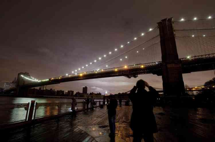 People photograph the Brooklyn Bridge and the Manhattan skyline, Tuesday, Oct. 30, 2012 in New York. Much of lower Manhattan is without electric power following the impact of superstorm Sandy. (AP Photo/Mark Lennihan)