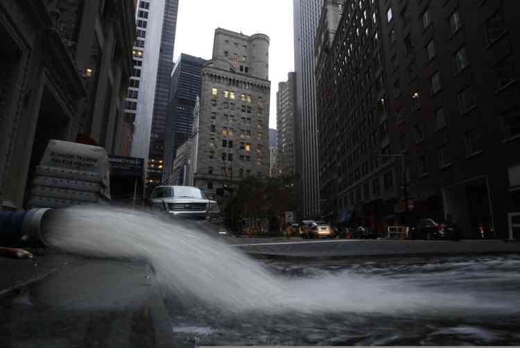 Water gushes from a hose as it is pumped out of a basement in New York's financial district, Wednesday, Oct. 31, 2012. Much of lower Manhattan and the financial district are still without electrical power. The Federal Reserve Bank of New York is background center. (AP Photo/Mark Lennihan)