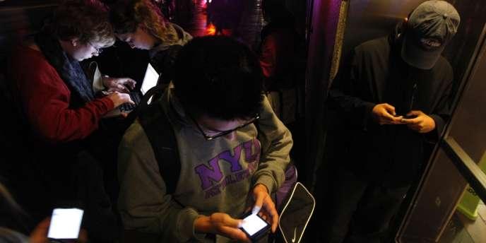 Des New-Yorkais se massent devant un bâtiment ayant encore un accès Wifi, le 30 octobre.