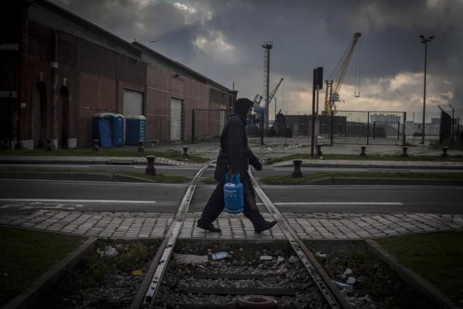 Un migrant ramene une bonbonne de gaz pour alimenter son rechaud dans son squat, à Calais.