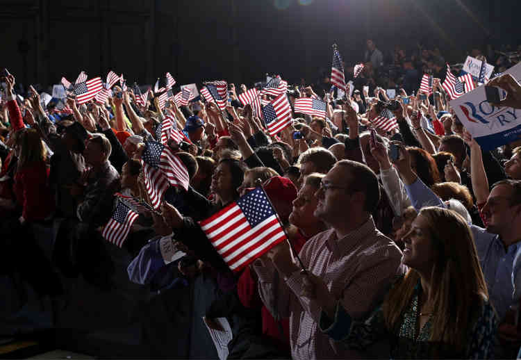 COLUMBUS, OH - NOVEMBER 05: Suporters wave American flags as Republican presidential candidate, former Massachusetts Gov. Mitt Romney speaks during a campaign rally at Landmark Aviation on November 5, 2012 in Columbus, Ohio. With one day to go until election day, Romney is making one final push through the swing states.   Justin Sullivan/Getty Images/AFP== FOR NEWSPAPERS, INTERNET, TELCOS & TELEVISION USE ONLY ==
