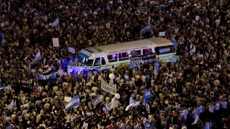A vehicle is surrounded by protesters demonstrating during a march against Argentina's President Cristina Fernandez in Buenos Aires, Argentina, Thursday, Nov. 8, 2012. Angered by rising inflation, violent crime and high-profile corruption, and afraid Fernandez will try to hold onto power indefinitely by ending constitutional term limits, the protesters banged pots and marched on the iconic obelisk in Argentina's capital. Protests also were held in plazas nationwide and outside Argentine embassies and consulates around the world. (AP Photo/Natacha Pisarenko)