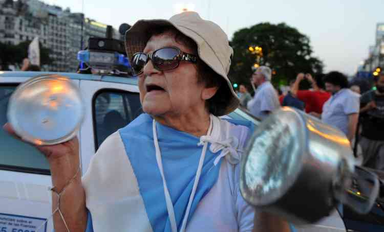 "A woman bangs cooking pans as she takes part in a ""cacerolazo"" (a form of civilian protest where pots are used to make noise) against Argentine President Cristina Fernandez de Kirchner's government in Buenos Aires on November 8, 2012. Thousands of opponents of President Cristina Fernandez de Kirchner gathered in middle and upper class neighbourhoods around the Argentine capital and other cities across the world banging their cooking pots in a noisy protest against any possible bid she might run for a third term. ""Say no to reelection,"" said the call to protest which was sent across the country via social media websites. Kirchner, 59, is currently barred by the Argentine Constitution from running for a third consecutive term, but her supporters in the Congress have been lobbying for a constitutional amendment.   AFP PHOTO / DANIEL GARCIA"
