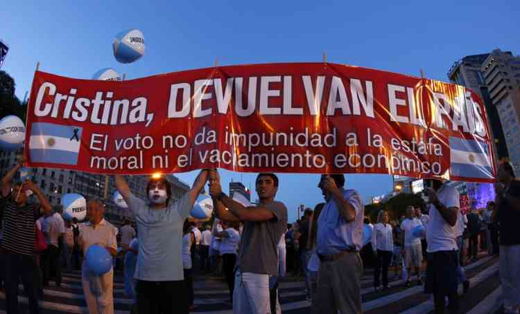 "Demonstrators hold up a banner against Argentine President Cristina Fernandez de Kirchner during a protest in Buenos Aires November 8, 2012. Following a huge turnout at a similar protest in September, demonstrators took to the streets of major cities to protest against what they say is a de facto ban on buying dollars and a possible bid to overhaul the constitution so President Cristina Fernandez could run for a third term. The demonstrators are not aligned with any particular opposition party and they have organized the protests via social media. Fernandez's popularity has fallen to about 30 percent since she was elected last year with a comfortable 54 percent of the vote. The banner reads, ""Cristina, give us back the country - the vote does not give impunity for moral scam nor the emptying of the economy."" REUTERS/Marcos Brindicci (ARGENTINA - Tags: POLITICS CIVIL UNREST)"