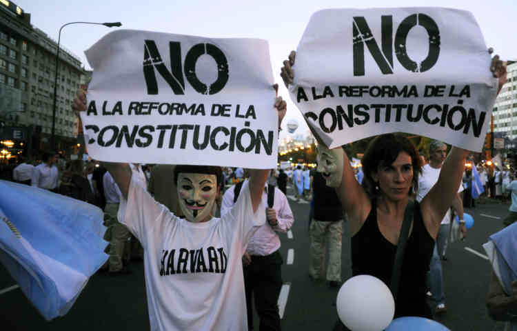 "People hold signs reading ""No to the reform of the Constitution"" as they wear Guy Fawkes masks during a ""cacerolazo"" (a form of civilian protest where pots are used to make noise) against Argentine President Cristina Fernandez de Kirchner's government in Buenos Aires on November 8, 2012. Thousands of opponents of President Cristina Fernandez de Kirchner gathered in middle and upper class neighbourhoods around the Argentine capital and other cities across the world banging their cooking pots in a noisy protest against any possible bid she might run for a third term. ""Say no to reelection,"" said the call to protest which was sent across the country via social media websites. Kirchner, 59, is currently barred by the Argentine Constitution from running for a third consecutive term, but her supporters in the Congress have been lobbying for a constitutional amendment.   AFP PHOTO / ALEJANDRO PAGNI"