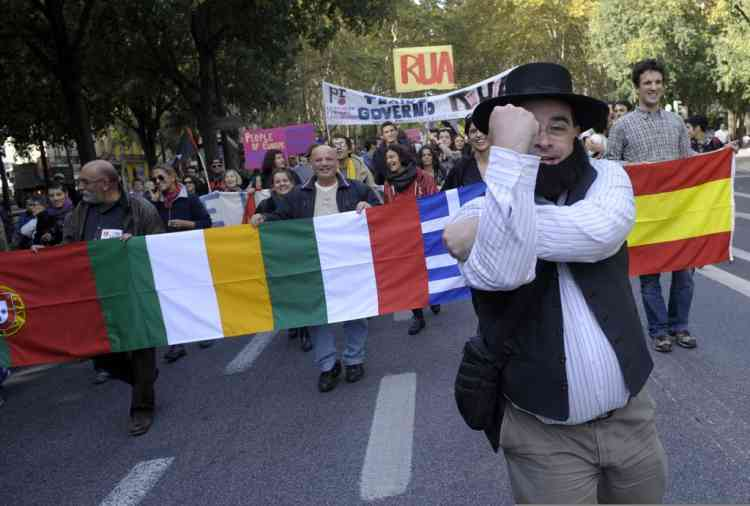 Protesters demonstrate holding flags of Portugal, Italy, Greece and Spain in Lisbon on November 14, 2012 during a general strike. General strikes in Spain and Portugal will spearhead the day of action called by European unions and joined by activists as anger over governments' tight-fisted policies boils over. AFP PHOTO / MIGUEL RIOPA