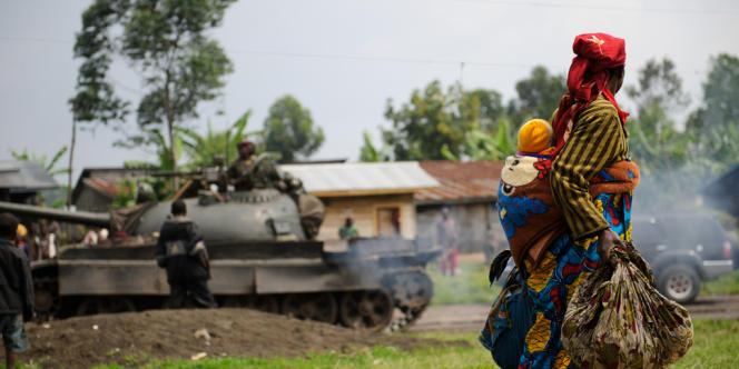 Une congolaise et son enfant devant un tank de l'armée gouvernementale, à Rugari, à 37 km de Goma, en juillet.