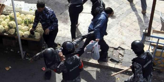 Des policiers empêchent des protestants de passer après les prières du vendredi à Amman, le 16 novembre 2012.
