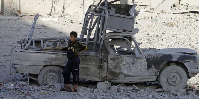 Un garçon palestinien à côté d'une voiture détruite par un bombardement, dans le nord de la bande de Gaza, dimanche 18 novembre.