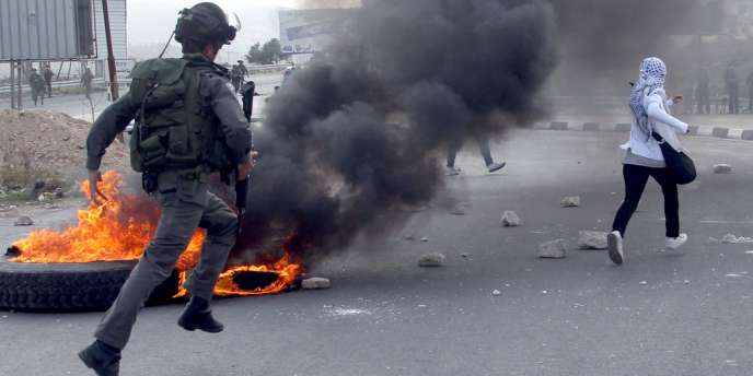 Un soldat israélien poursuit une manifestante palestinienne qui protestait contre l'opération militaire à Gaza, au check point de Hawara, à l'entrée de Naplouse, en Cisjordanie, samedi 17 novembre.