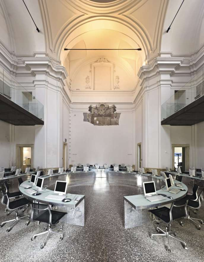 A la place de l'autel, des dizaines d'écrans... Construite en 1674, l'église Santa Teresa, à Milan, a été fermée au culte au début du XIXe siècle. Acquise par la ville en 1974, elle abrite depuis 2003 une médiathèque.