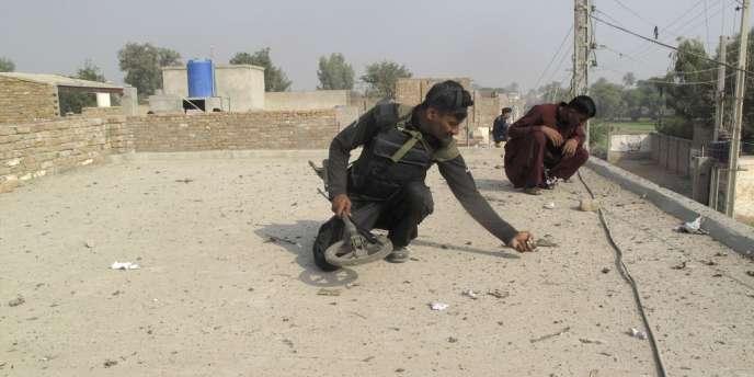 Des policiers ramassent des projectiles sur le toit d'une maison voisine du lieu où a explosé une bombe, samedi matin, dans le nord-ouest du Pakistan.