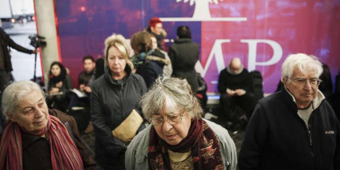 Des passants, militants et journalistes attendent la décision de la Commission de recours au siège de l'UMP, à Paris, lundi 26 novembre.