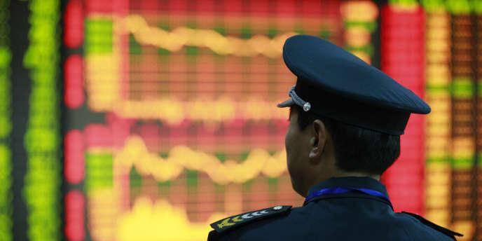 Un homme observe le cours des échanges à la Bourse de Huaibei.