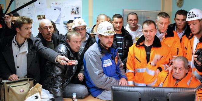 Des salariés d'ArcelorMittal suivent la conférence de presse de Jean-Marc Ayrault, vendredi soir 30 novembre, annonçant un accord entre le gouvernement et ArcelorMittal sur l'avenir du site de Florange.