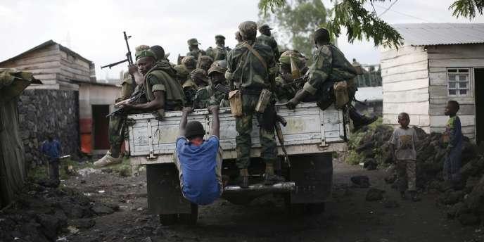 Un enfant s'accroche au camion ramenant les troupes gouvernementales à Goma, dans l'est de la RDC, en décembre 2012.