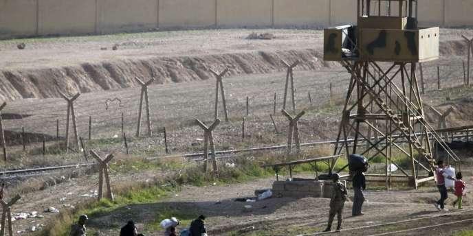 Des Syriens traversent la frontière avec la Turquie, près du village syrien Ras-Al-Aïn.