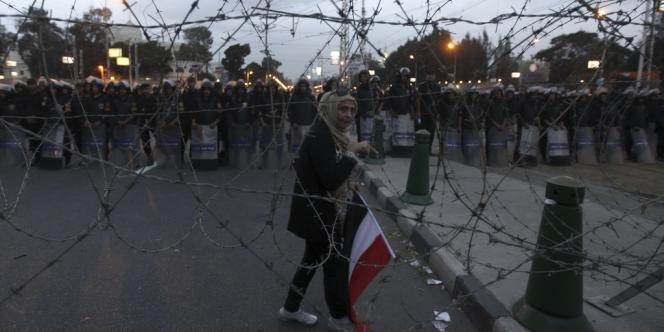 Une manifestante anti-Mohamed Morsi passe devant les forces de l'ordre, mardi soir 4 décembre. Celles-ci ont peu répliqué aux assauts des manifestants, les laissant encercler le palais présidentiel.