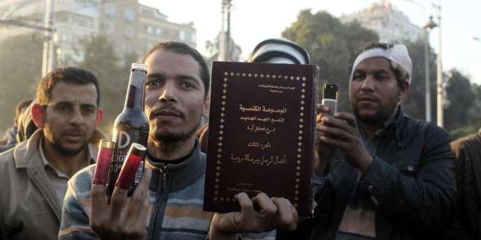 Des partisans des Frères musulmans montrent des objets qu'il affirme avoir trouvés parmi les manifestants anti-Morsi : des cartouches, une bouteille d'alcool et un livre sur le christianisme.