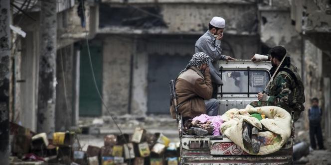Des combattants de l'Armée syrienne libre recouvrent deux corps trouvés dans les décombres d'immeubles, à Alep, le 10 décembre.