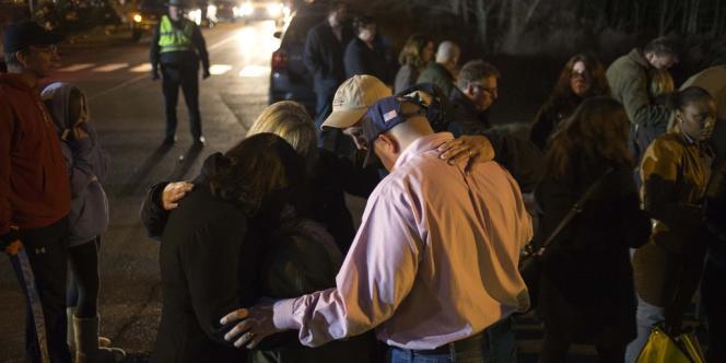 Des habitants de Newtown prient sur la route longeant l'école Sandy Hook, le 15 décembre.