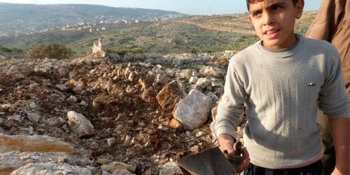 Un jeune Syrien présente un reste de missile SCUD et l'emplacement supposé de son explosion, près de la ville de Darret Ezza, dans le nord-ouet du pays, le 13 décembre.