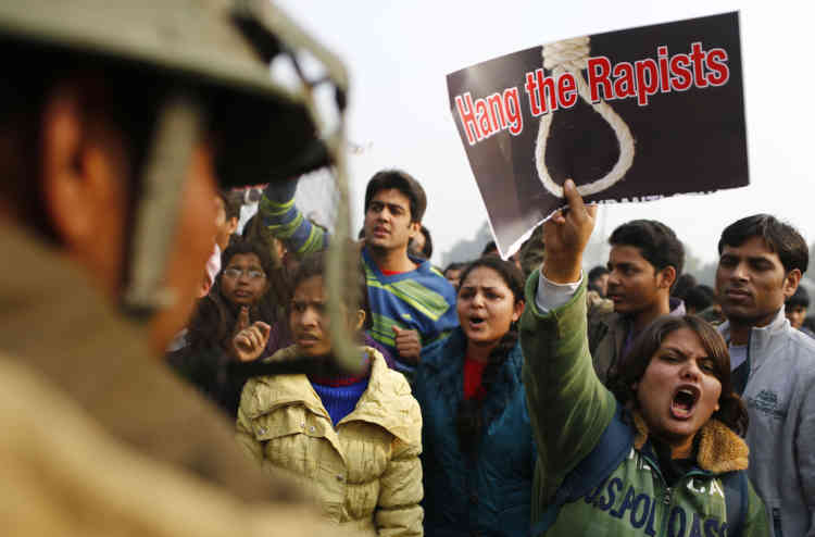 An Indian demonstrator (2nd R) shouts slogans at the police during a protest calling for  better safety for women following the rape of a student last week, in front the India Gate monument in New Delhi on December 23, 2012. In the biggest protest so far, several thousand college students rallied at the India Gate monument in the heart of the capital where they were baton-charged, water cannoned and tear gassed by the police.    TOPSHOTS AFP PHOTO/ Andrew Caballero-Reynolds