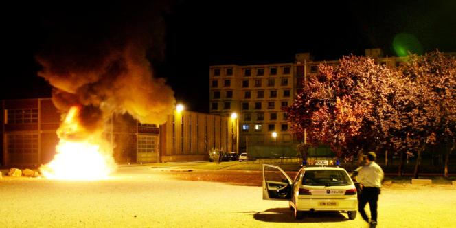 Des policiers interviennent après qu'une voiture a été incendiée le 26 mai 2006 à Vaulx-en-Velin dans la banlieue de Lyon.