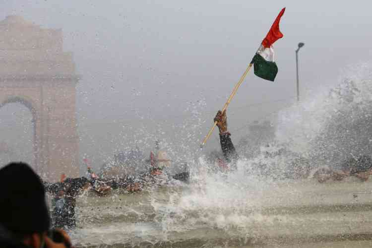 Indian demonstrators are hit by water cannon during a protest calling for  better safety for women following the rape of a student last week, in front the India Gate monument in New Delhi on December 23, 2012. In the biggest protest so far, several thousand college students rallied at the India Gate monument in the heart of the capital where they were baton-charged, water cannoned and tear gassed by the police. AFP PHOTO/ TENGKU BAHAR