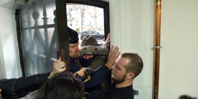 Un CRS tente de pénétrer dans le bâtiment occupé depuis ce matin par des militants du 9e Collectif des sans-papiers, avenue du Président-Wilson à Paris.