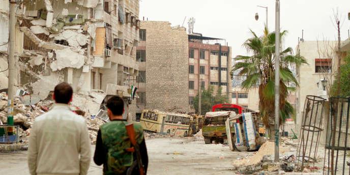 Des rebelles constatent les dégâts après des bombardements dans une ville en périphérie d'Alep, le 1er janvier 2013.