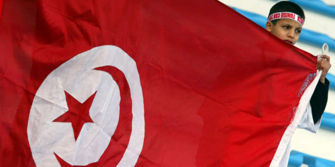 Un jeune garçon brandit un drapeau tunisien lors d'un match à Sfax, en janvier 2004.