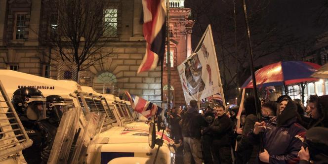Des manifestants loyalistes nord-irlandais font face aux policiers antiémeute britanniques, le 7 janvier, à Belfast.