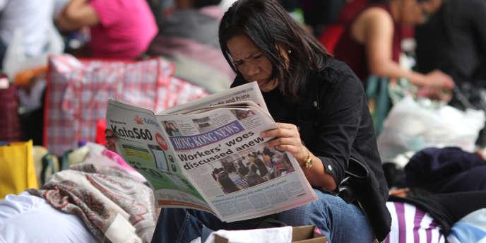 Une domestique lit un article sur le droit des immigrés à Hongkong, en octobre 2011.