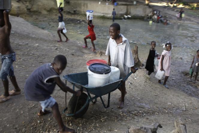 Des enfants transportent de l'eau puisée dans une rivière à Thomazeau, à 10 km au Nord-Est de Port-au-Prince. La distribution d'eau potable est un des défis d'Haïti.