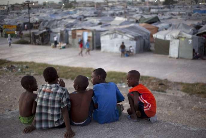 Des enfants haïtiens observent le camp de tentes Jean-Marie Vincent, à Port-au-Prince, le 9 janvier.