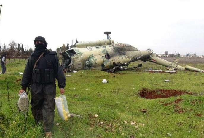 Un combattant rebelle devant l'épave d'un hélicoptère de l'armée syrienne sur la base de Taftanaz prise par l'ASL le 10 janvier.