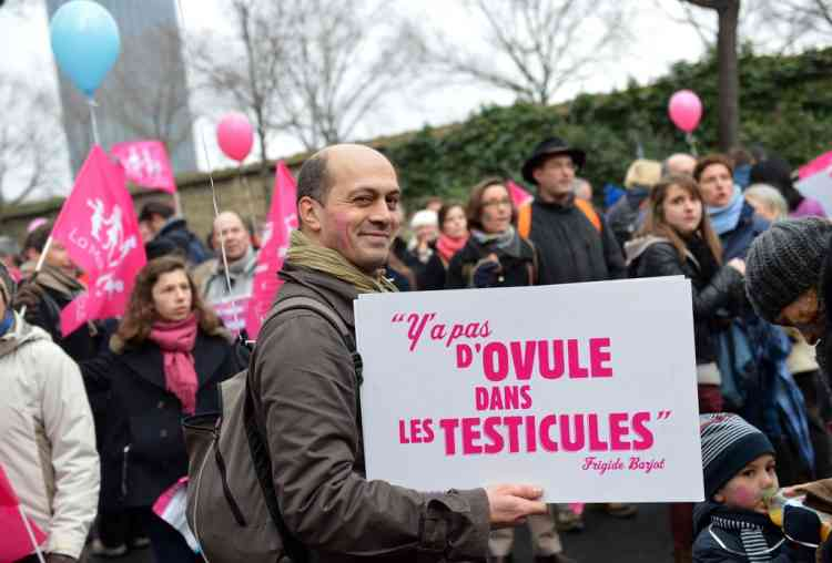 """A protester holds a placard reading """"There are no eggs in the testicles (Frigide Barjot)"""" during a march against same-sex marriage on January 13, 2013 in Paris. Tens of thousands march in Paris on January 13 to denounce government plans to legalise same-sex marriage and adoption which have angered many Catholics and Muslims, France's two main faiths, as well as the right-wing opposition. The French parliament is to debate the bill -- one of the key electoral pledges of Socialist President -- at the end of this month. AFP PHOTO / MIGUEL MEDINA"""