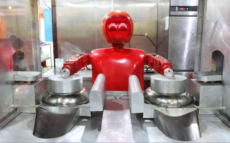 A robot cooks in a robot-themed restaurant in Harbin, northeast China's Heilongjiang province on January 16, 2013.  Twenty robots perform a variety of chores, from ushering in guests to waiting tables and cooking  dishes.         CHINA OUT     AFP PHOTO