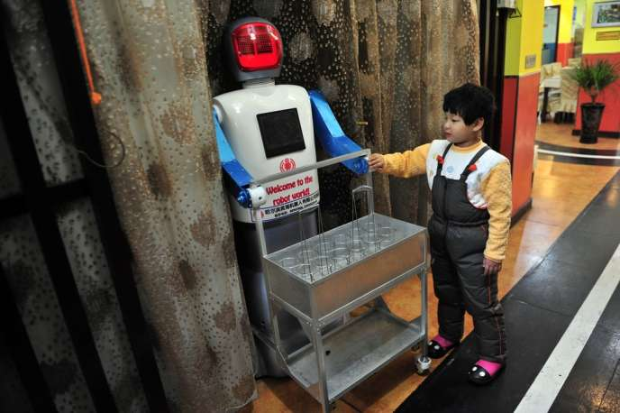 A boy touches a robot that specialises in delivering drinks at a Robot Restaurant in Harbin, Heilongjiang province January 12, 2013. Opened in June 2012, the restaurant has gained fame in using a total of 20 robots, which range in heights of 1.3–1.6 metres (4.27-5.25 ft), to cook meals and deliver dishes. The robots can work continuously for five hours after a two-hour charge.    REUTERS/Sheng Li (CHINA - Tags: SOCIETY SCIENCE TECHNOLOGY)