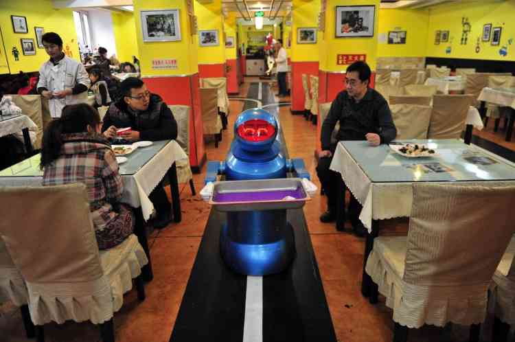 A robot that specialises in delivering food holds an empty plate after serving meals to customers at a Robot Restaurant in Harbin, Heilongjiang province January 12, 2013. Opened in June 2012, the restaurant has gained fame in using a total of 20 robots, which range in heights of 1.3 – 1.6 metres, to cook meals and deliver dishes. The robots can work continuously for five hours after a two-hour charge, and are able to display over 10 expressions on their faces and say basic welcoming sentences to customers, local media reported. REUTERS/Sheng Li (CHINA - Tags: SOCIETY SCIENCE TECHNOLOGY FOOD TPX IMAGES OF THE DAY)