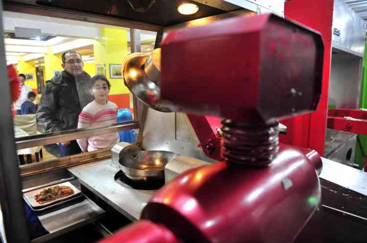 Customers watch a robot cooking dishes at a Robot Restaurant in Harbin, Heilongjiang province January 12, Opened in June 2012, the restaurant has gained fame in using a total of 20 robots, which range in heights of 1.3-1.6 metres (4.27-5.25 ft), to cook meals and deliver dishes. The robots can work continuously for five hours after a two-hour charge, and are able to display over 10 expressions on their faces and say basic welcoming sentences to customers, local media reported.     REUTERS/Sheng Li (CHINA - Tags: SOCIETY SCIENCE TECHNOLOGY FOOD)