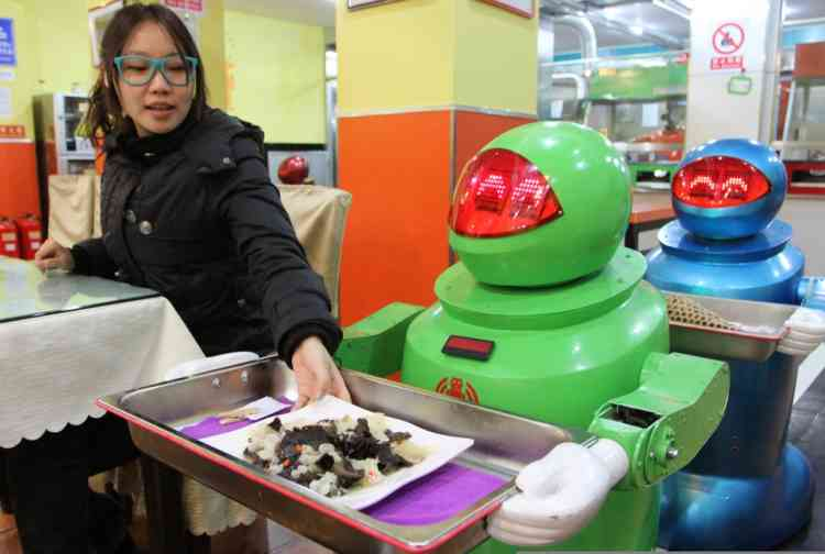 A robot serves guests in a robot-themed restaurant in Harbin, northeast China's Heilongjiang province on January 16, 2013.  Twenty robots perform a variety of chores, from ushering in guests to waiting tables and cooking  dishes.         CHINA OUT     AFP PHOTO