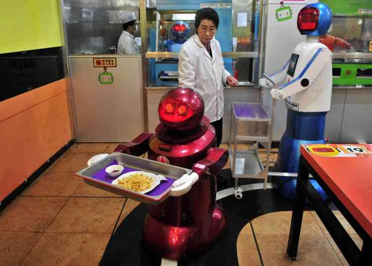 A robot (front) delivers French fries to customers at a Robot Restaurant in Harbin, Heilongjiang province, January 12, 2013. Opened in June 2012, the restaurant has gained fame in using a total of 20 robots, which range in heights of 1.3 – 1.6 metres, to cook meals and deliver dishes. The robots can work continuously for five hours after a two-hour charge, and are able to display over 10 expressions on their faces and say basic welcoming sentences to customers, local media reported.     REUTERS/Sheng Li (CHINA - Tags: SOCIETY SCIENCE TECHNOLOGY FOOD)
