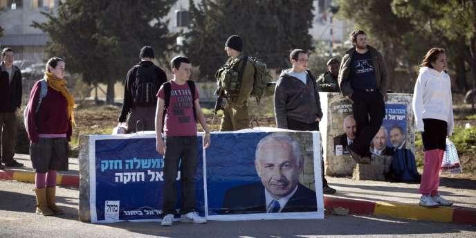 Des colons israéliens devant une affiche électorale de Benyamin Nétanyahou, à Gush Etzion, en Cisjordanie, le 15 janvier.