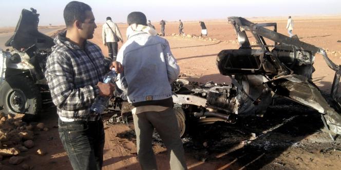 Dans cette photo non datée, des Algériens regardent la carcasse d'un véhicule détruit près du site de In Amenas, dans le sud-est algérien.